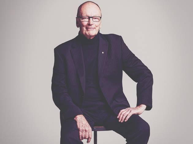Bell Shakespeare founder John Bell 2020 sitting on a stool