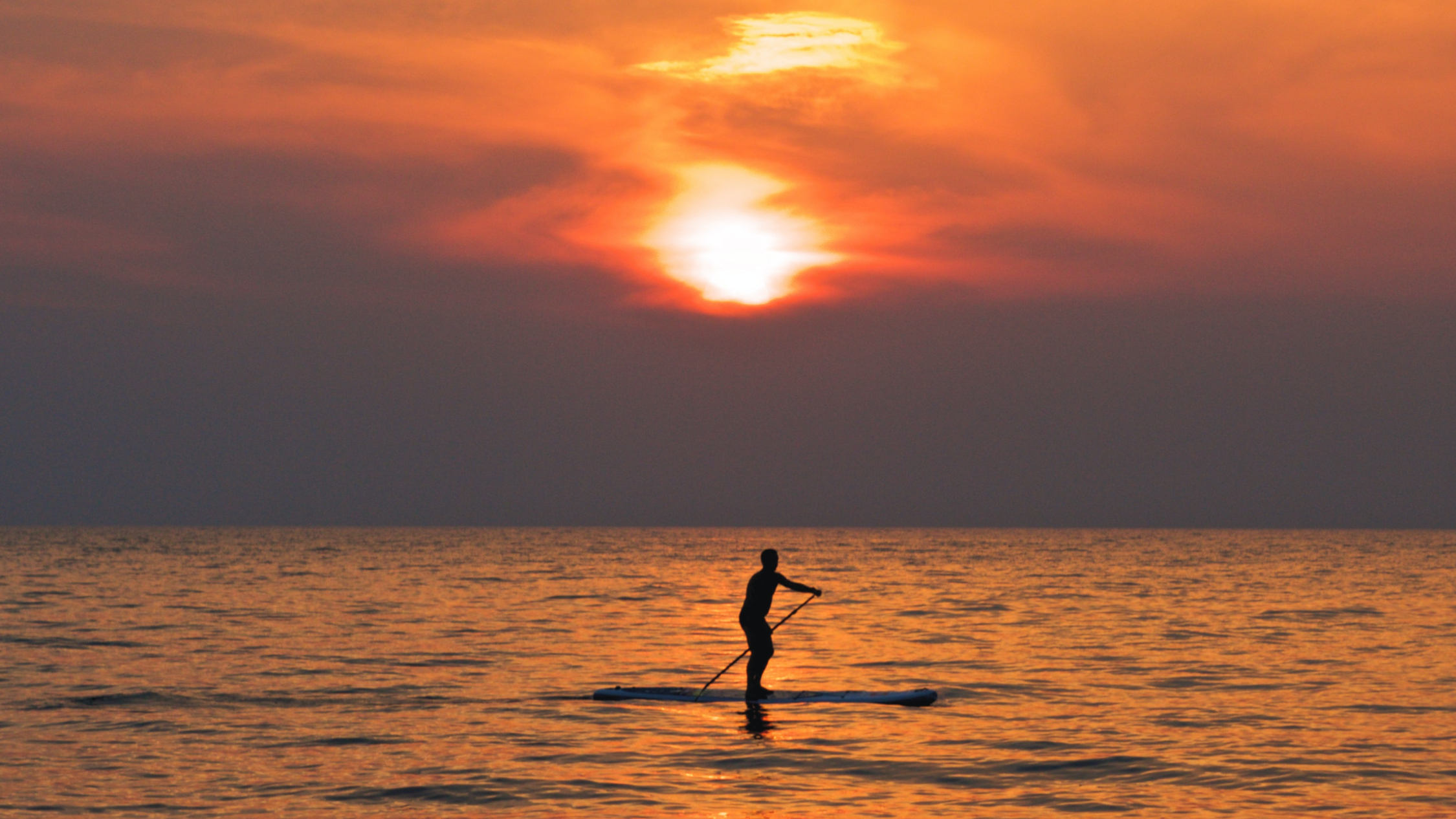 A solitary paddleboarder on the sea