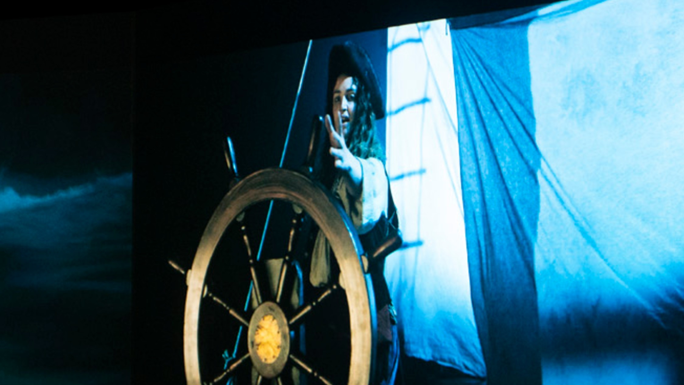 A still from  Lisa Reihana 'Nomads of the Sea' depicting a female captain at the wheel of a ship