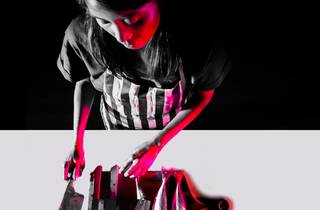a striking image black and white and pink image of a person with an array of knives