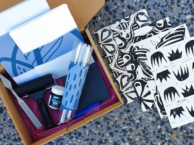 A box filled with lino printing tools next to three postcards featuring geometric prints
