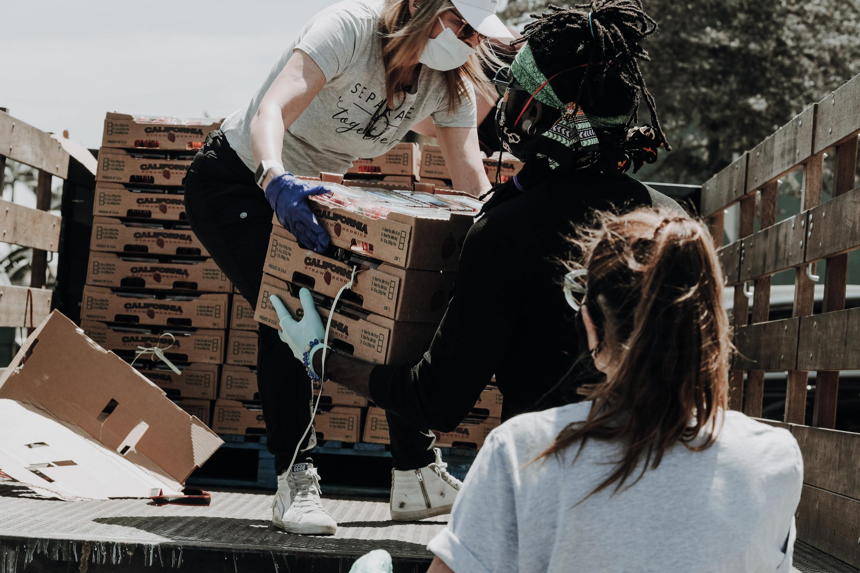 People unload crates from truck