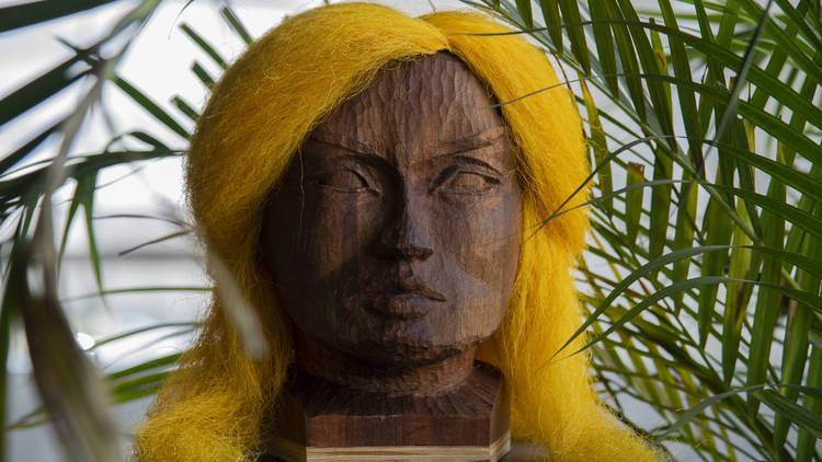 Busto de madera con facciones femeninas y peluca rubia
