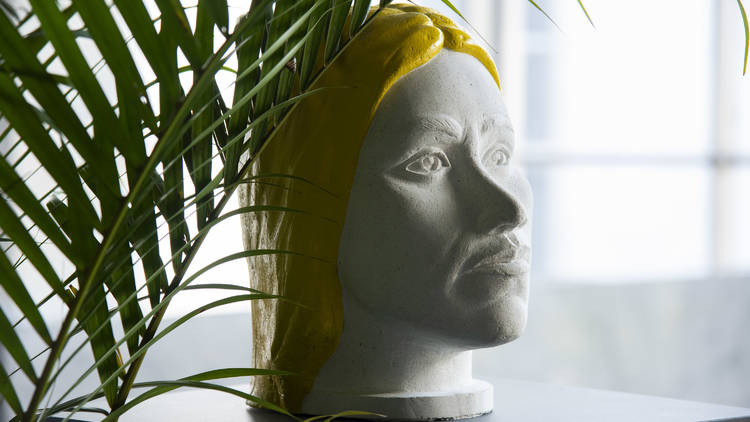 Busto blanco con rasgos femeninos y peluca amarilla
