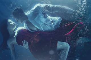 a man and woman submerged under water fully clothed