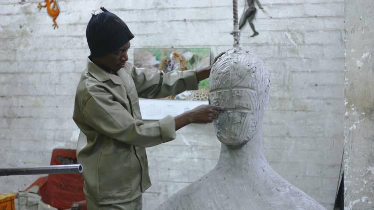 Person sculpting large figure