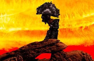 A burned warrior-like bust wearing a headdress rests on a rock in a fiery apocalypse