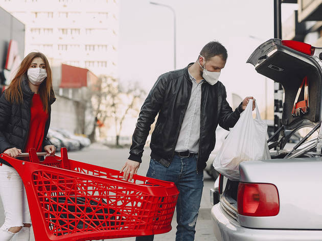 A man and a woman unloading groceries from a shopping trolley into a sedan car in a carpark