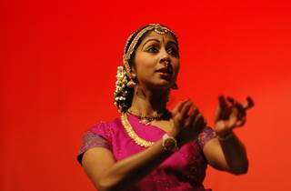 A dancer in a pink sari and gold jewellery performs against a bright red backdrop