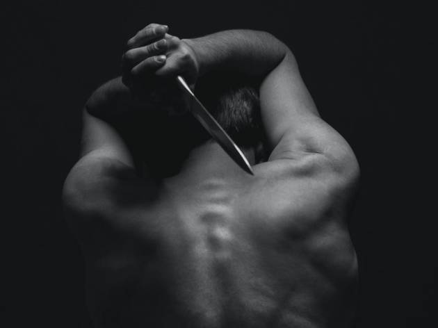 A rear view of a topless Macbeth, holding a dagger behind him