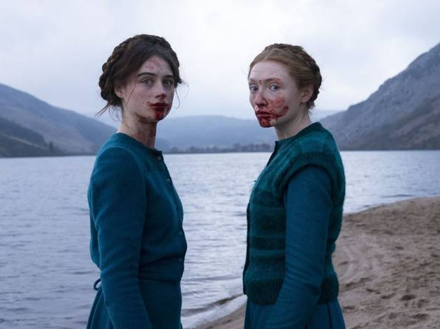 Two women with blood on their faces in front of a lake and hills