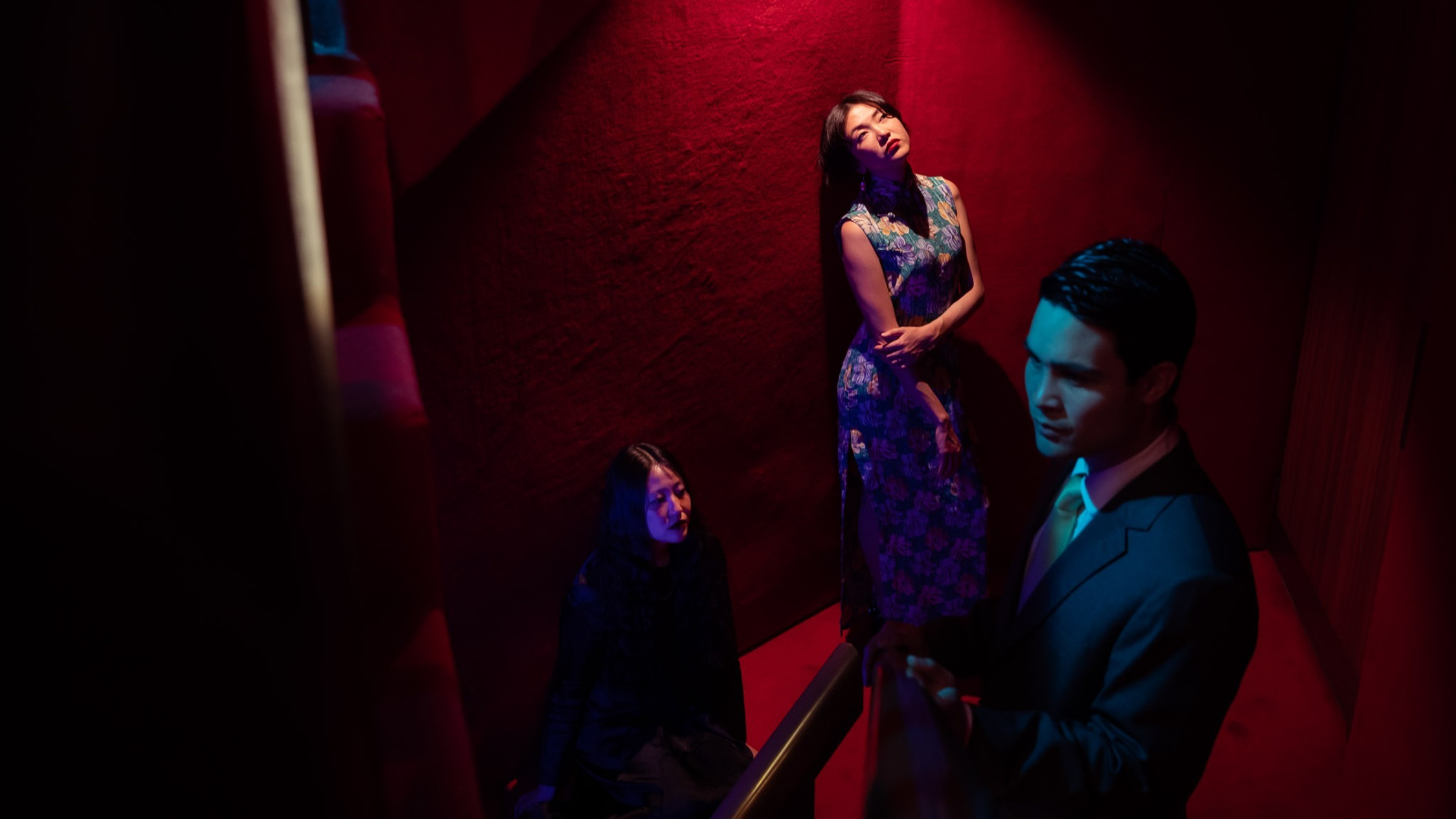 Rainbow Chan, Eugene Choi and Marcus Whale bathed in lighting reminiscent of Wong Kar-Wai's classic film In The Mood for Love