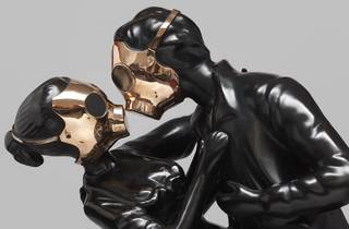Two sculptural figures in matte black wear bronze gas masks and embrace