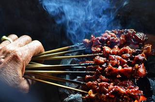 Person holding satay skewers
