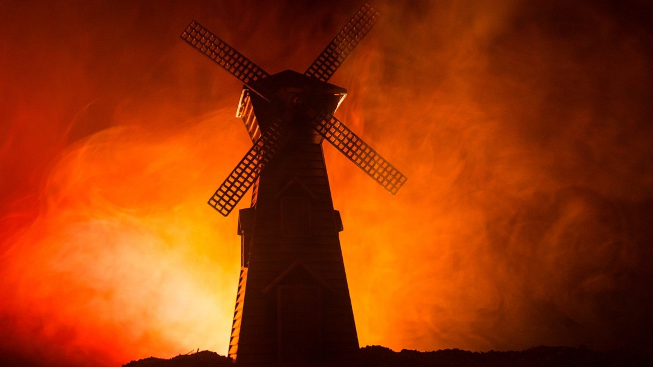 A windmill silhouetted by haze lit by fire