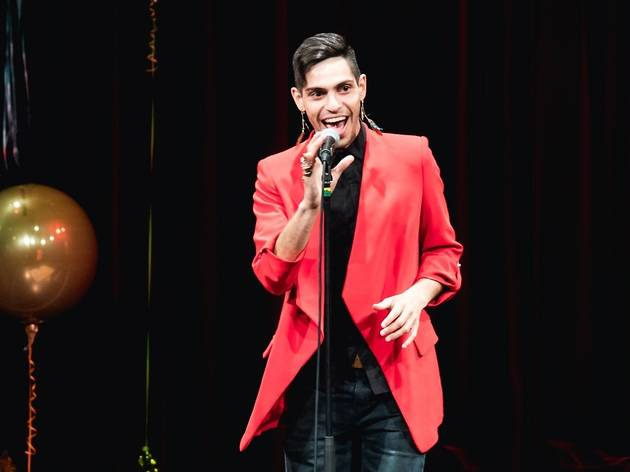 Comedian AJ Lamarque performs on stage with microphone, he wears a structured red jacket.