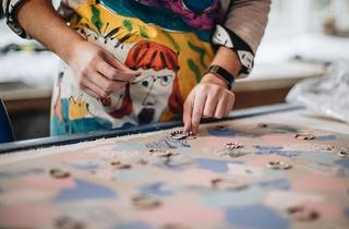 A person rearranges ceramic jewellery on a patterned blanket