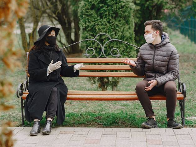 Couple outside on park bench masks