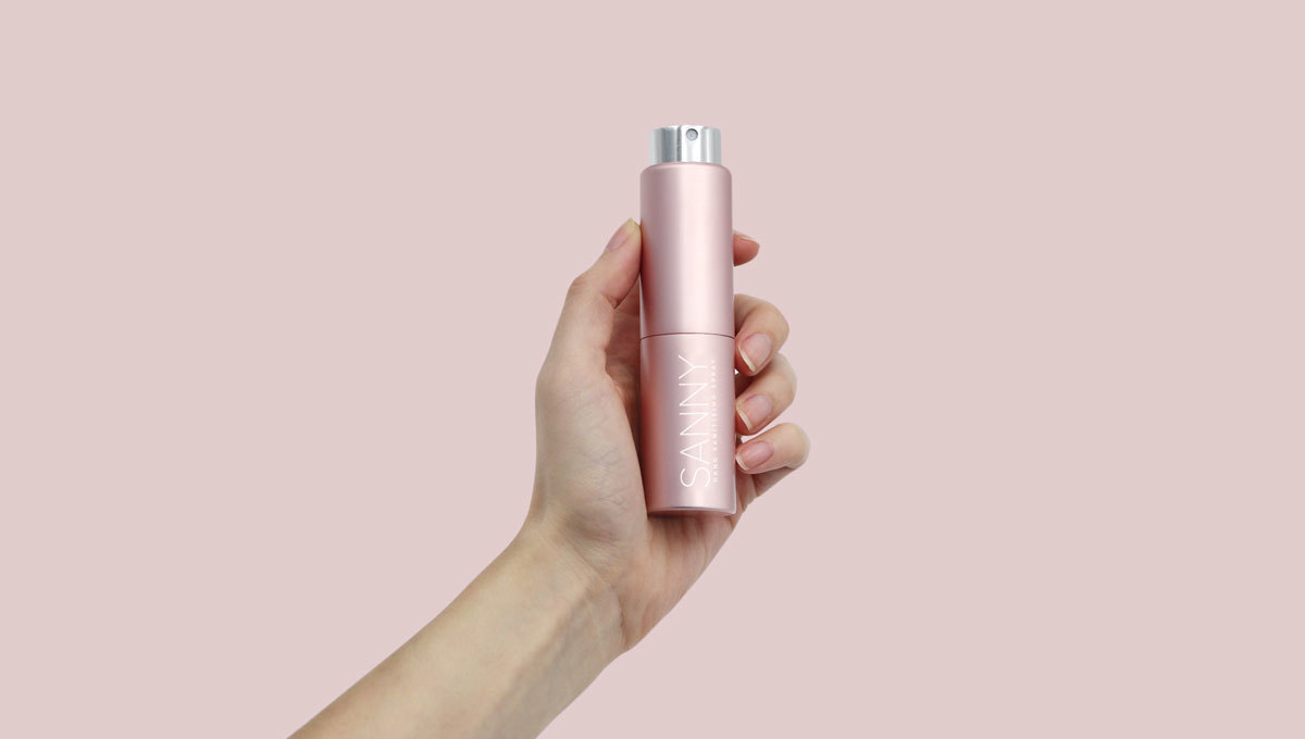 Hand holding pink bottle of hand sanitiser