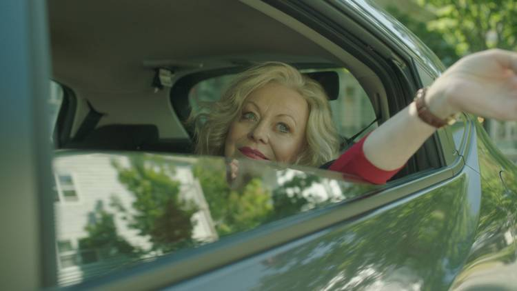Jacki Weaver leans one arm out the back of a car as Maybelline in movie Stage Mother