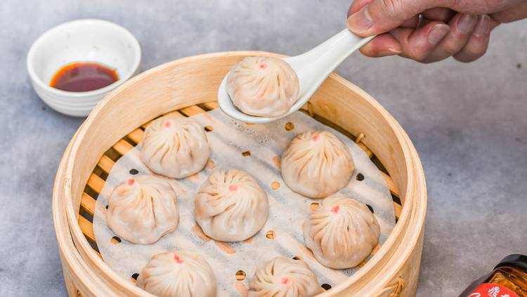 Person picking up dumpling from steamer