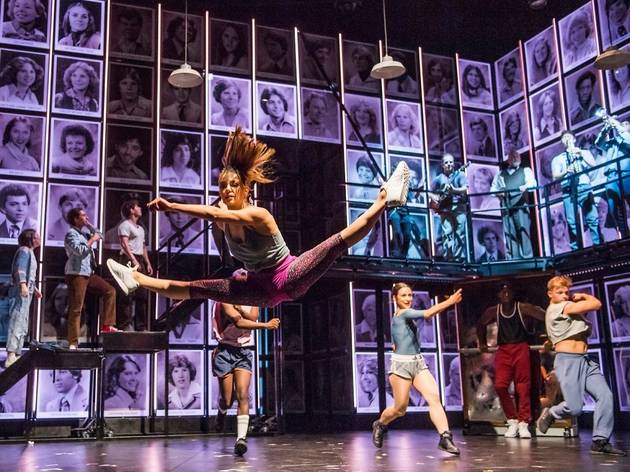 Young woman leaping into splits midair in Fame the Musical