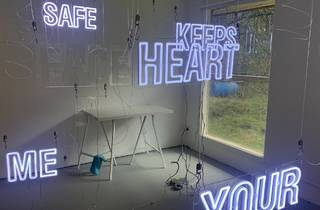 A room with neon words hanging in it