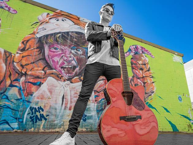 Former INXS lead singer Ciaran Gribbin poses with a guitar in front of bright graffiti