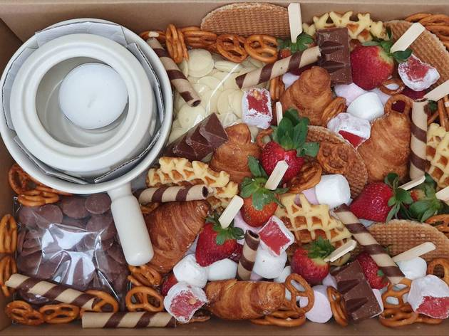 Picnic hamper featuring chocolate fondue set, strawberries, waffles, pretzels, marshmallows, stroopwafels and chocolates.