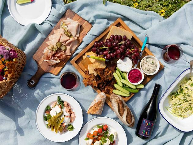 Picnic featuring charcuterie, salads, fruits, baguette, pasta and wine.