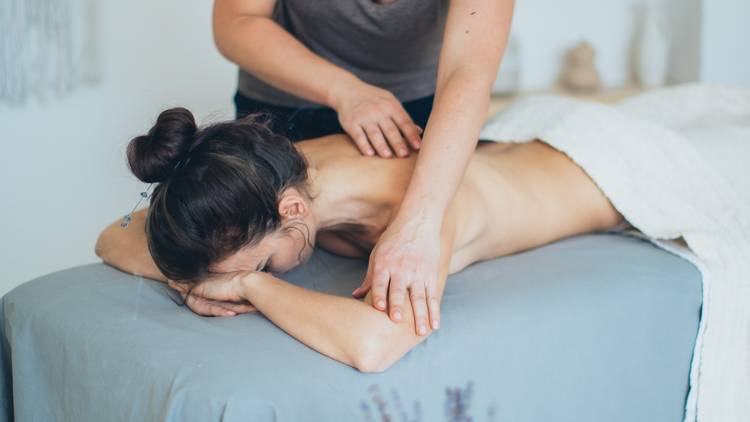 A woman lying facedown getting her back massaged