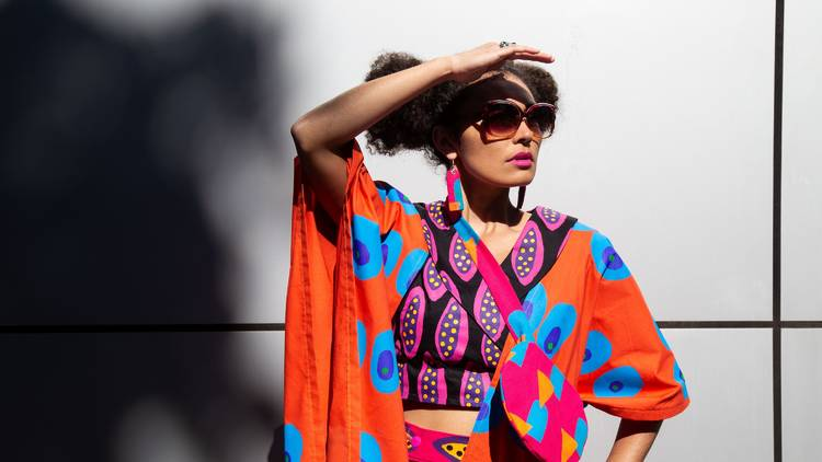 Woman in brightly printed dress shielding face from the sun