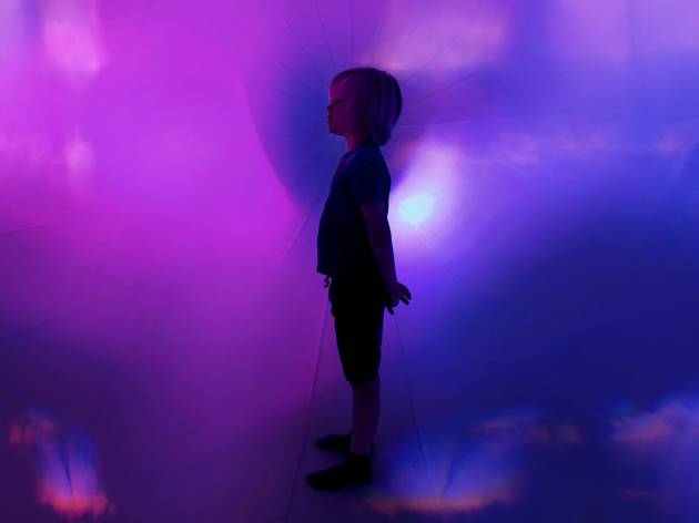A small child standing in a dreamlike, foggy room lit blue and purple