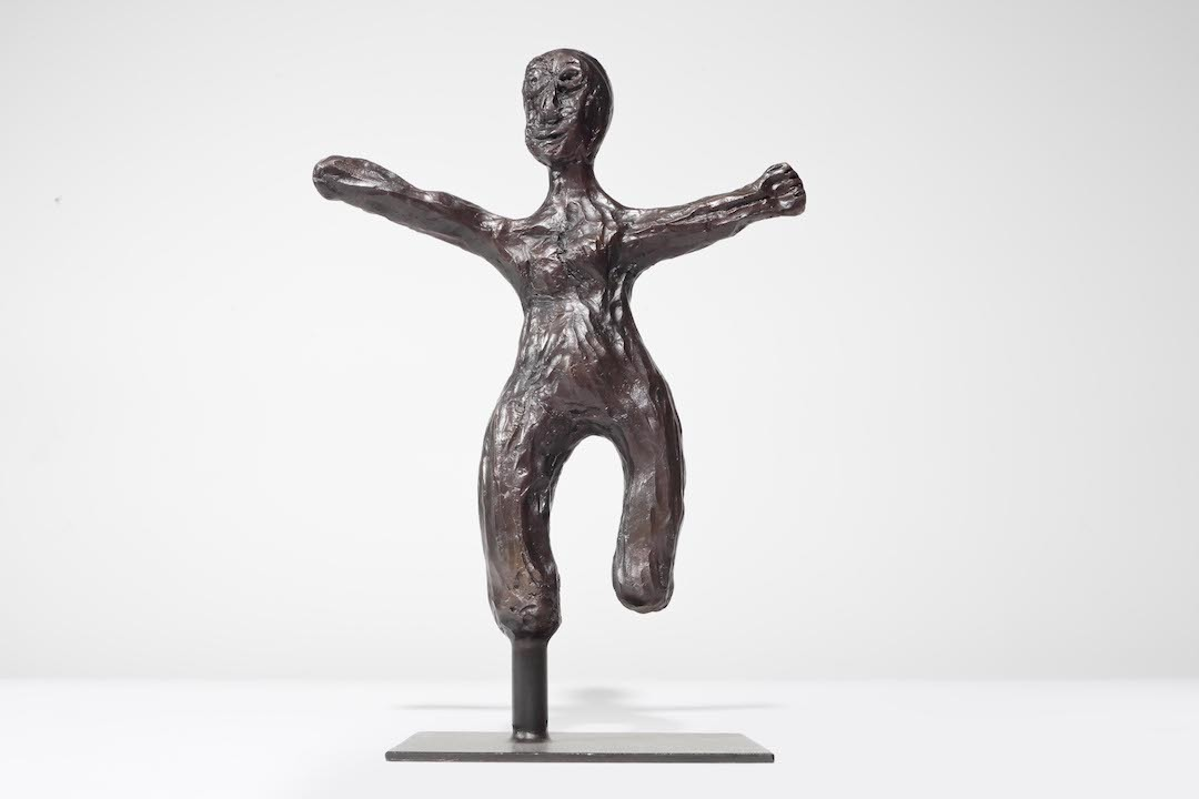 A bronze figurine of a man with arms outstretched