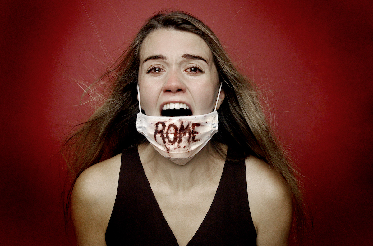 """Woman screaming in mask with """"Rome"""" written on it in blood in Rogue Ensemble Theatre Company's Titus Andronicus"""