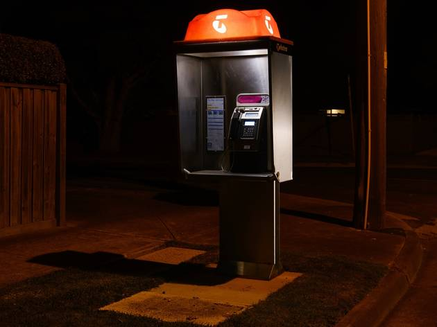 A Telstra phone box on a suburban street in the middle of the night