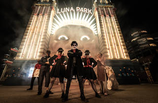 Spooky characters stand in front of the Luna Park sign