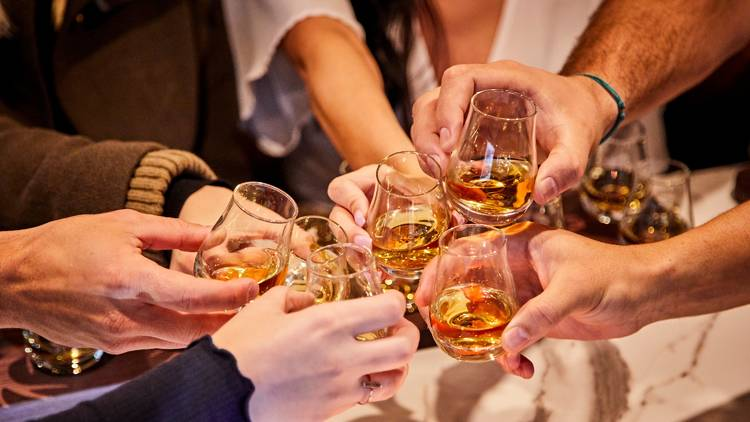 People clinking whisky glasses