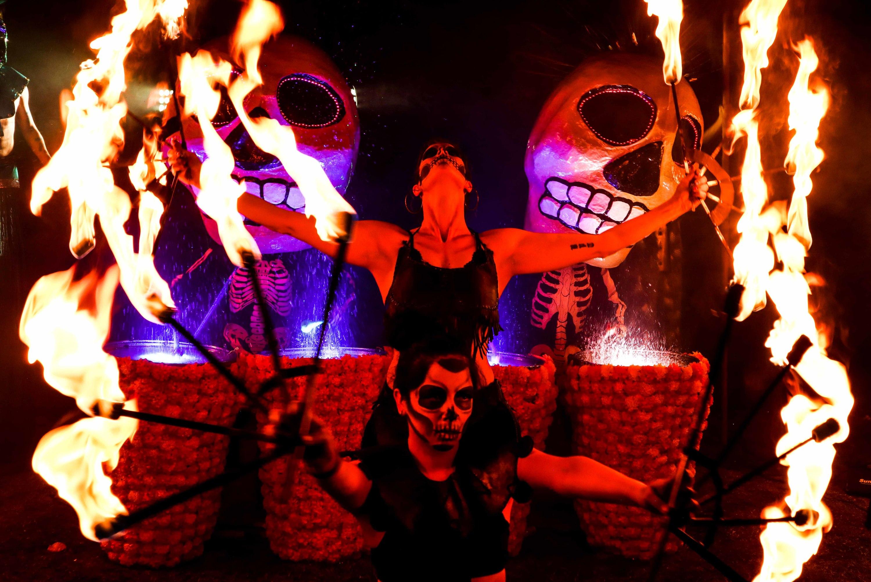 Personas disfrazadas de catrinas haciendo malabares con lanzas de fuego