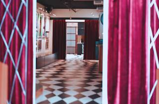 Peering through red curtains to a gallery with a checkerboard floor