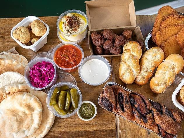 Picnic pack featuring challah, pickles, pickled cabbage, babka, hummus, pitas and schnitzels.