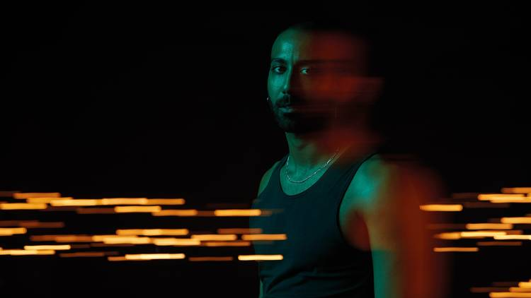 A man wearing a singlet and a chain around his neck. He's in a dark room and is slightly blurred