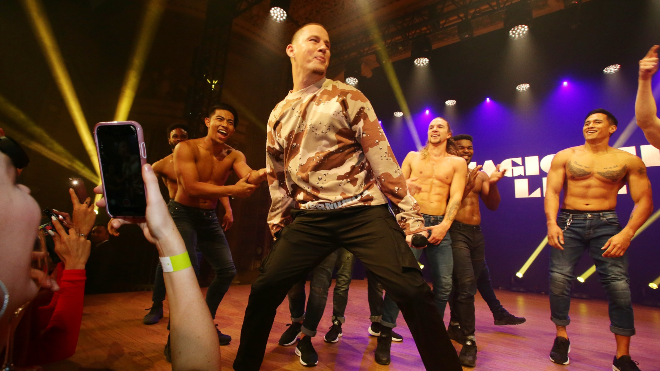 Channing Tatum with buff male dancers on stage announcing Magic Mike Live