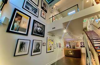 Interior of Lyons Gallery showing two levels of framed photographs and a reception desk