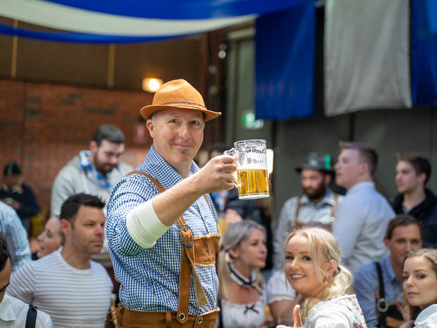 A man wearing lederhosen in a crowded hall, raising a stein of beer and smiling at the camera