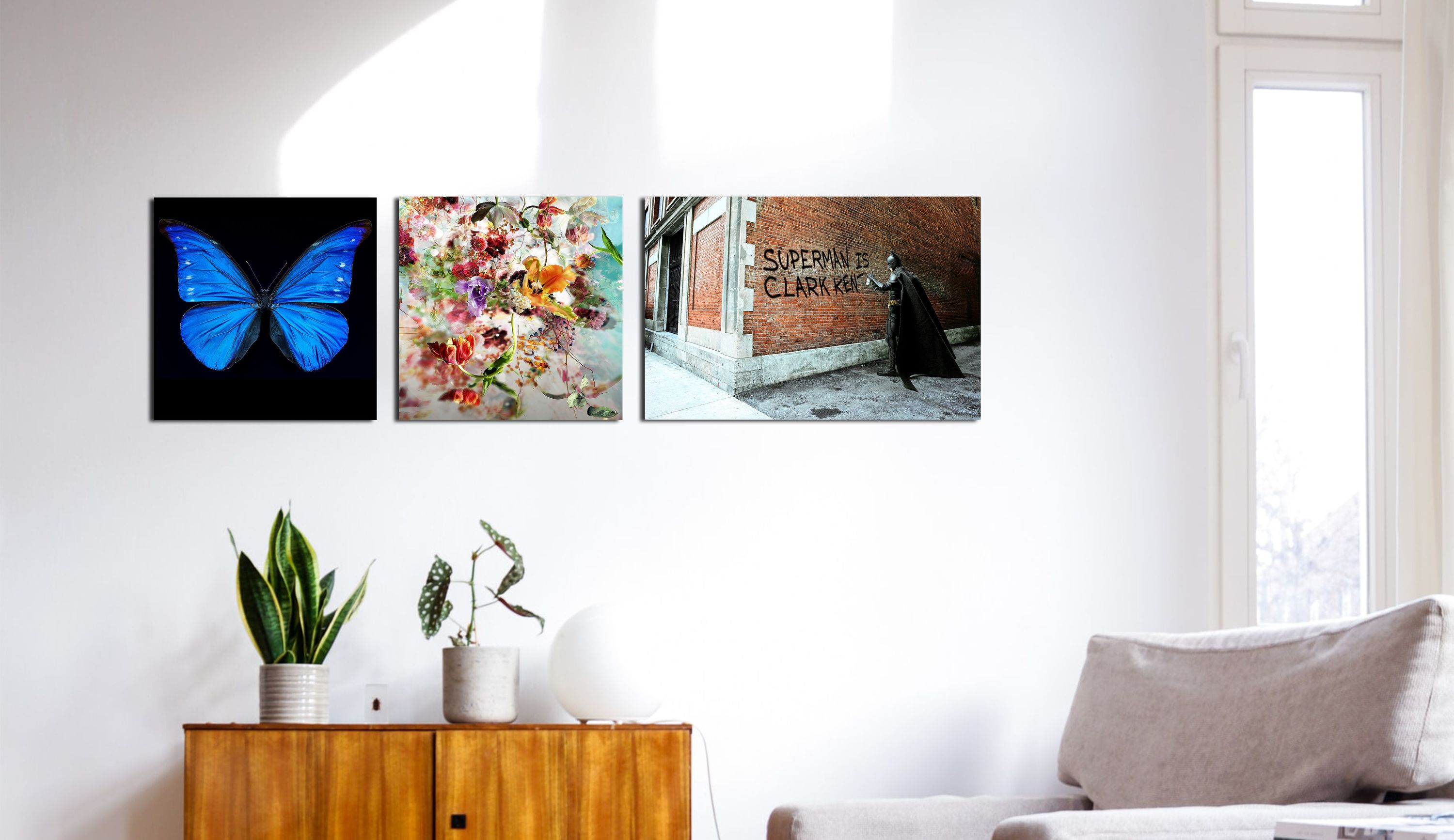 Three mini artworks on a wall from left to right; butterfly, floral tableau and a Banksy-style street art work