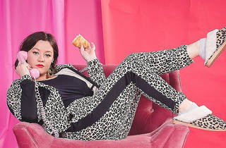A woman wearing a leopard print tracksuit and slippers reclining on a plush pink armchair. She is looking at the camera while holding a half eaten croissant and a pink, old-fashioned cord telephone to her ear