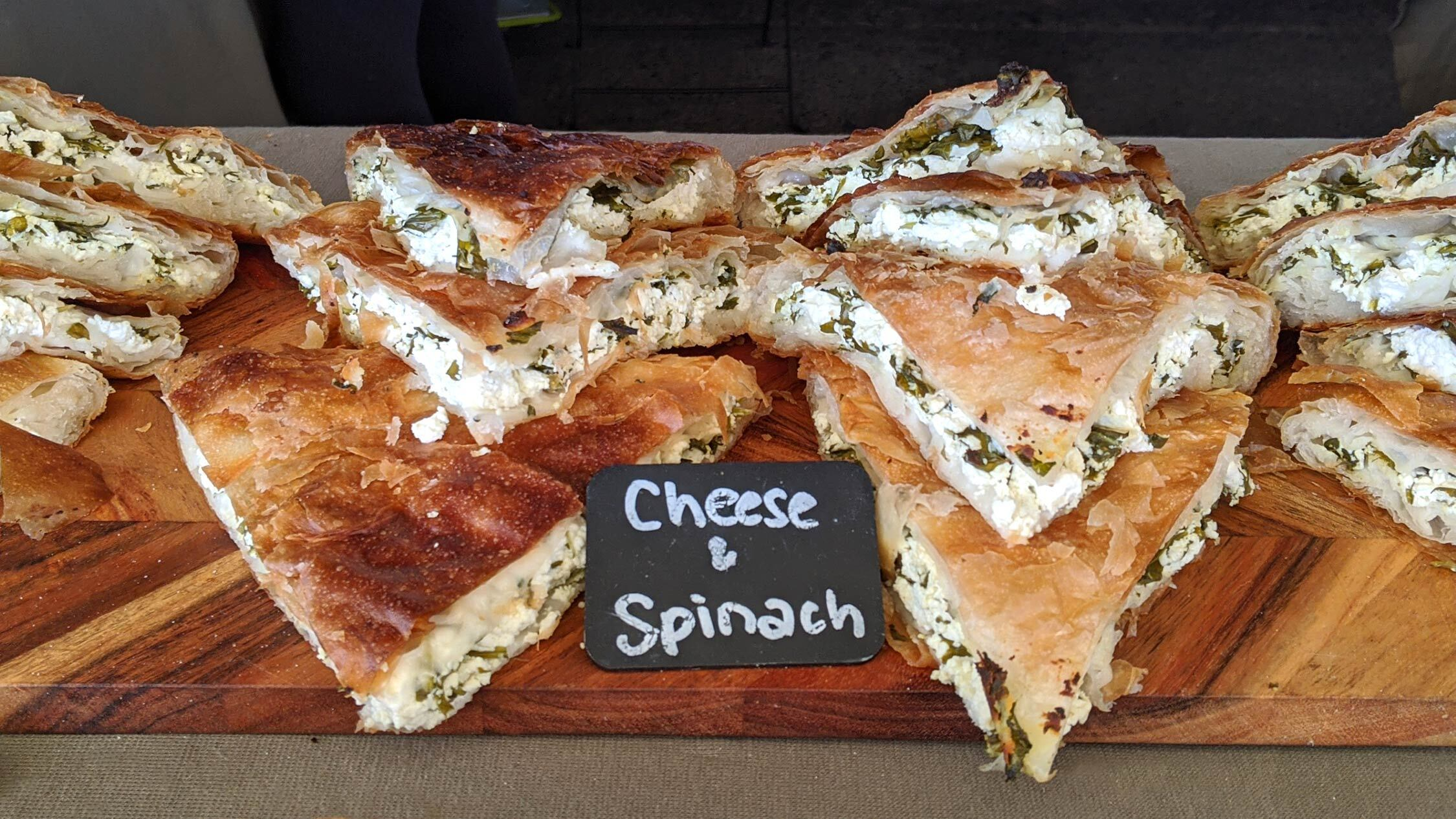 Cheese and Spinach burek on a wooden board