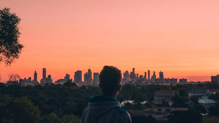 A man looking at the Melbourne city skyline at sunset