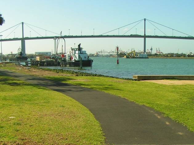 A bike trail near the bay, with the Westgate Bridge in the background